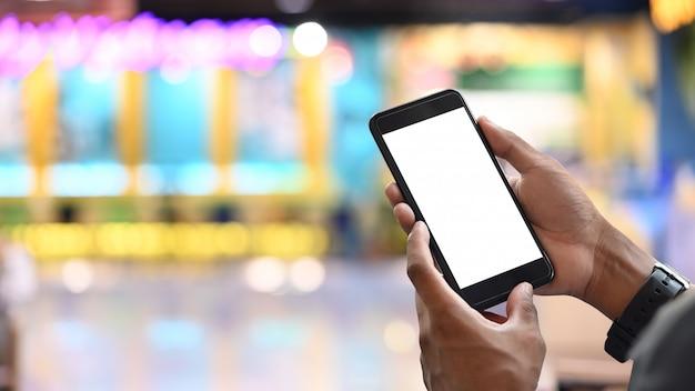 Manos del hombre de negocios que sostienen smartphone de la pantalla en blanco con el fondo borroso.