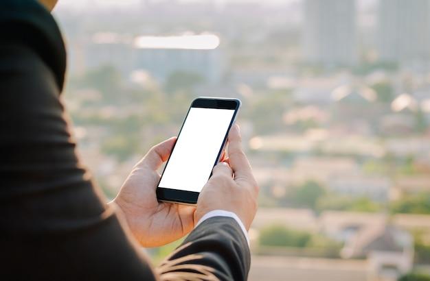 Las manos del hombre de negocios que sostienen el teléfono móvil de la pantalla en blanco en la ciudad urbana borrosa como fondo