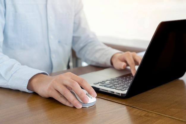 Manos de hombre de negocios con ratón y computadora portátil, trabajando y plan
