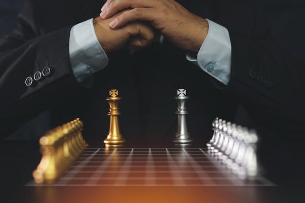 Manos del hombre de negocios en la suite negra que se sienta y que junta las manos que planean estrategia con ajedrez en la tabla del vintage. concepto de objetivo de decisión y logro.