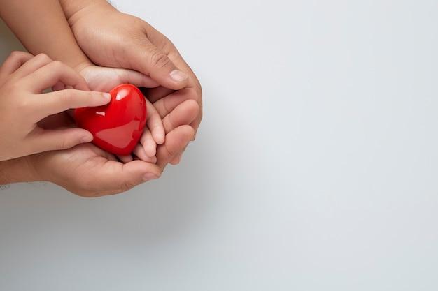 Manos de hombre y niño con un corazón rojo en la pared blanca