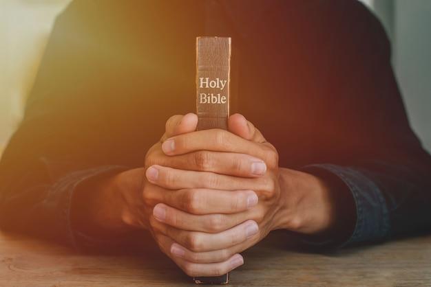 Las manos de un hombre orando sobre una biblia representan la fe y la espiritualidad en la vida cotidiana. de cerca.