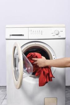 Las manos del hombre ponen la ropa en la lavadora.