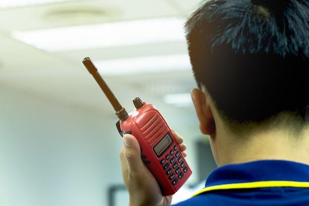 Manos de hombre de primer plano con walkie-talkie rojo o transceptor de radio portátil para la comunicación
