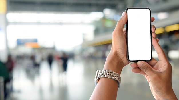 Las manos del hombre del primer que sostienen smartphone en la estación del aeropuerto con el fondo de la falta de definición.