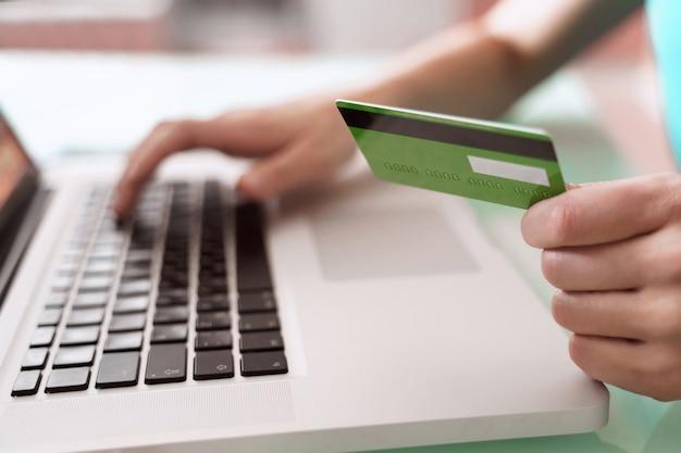 Las manos del hombre del primer que usan la computadora portátil para los pagos en línea con la tarjeta de crédito, la banca electrónica y el concepto de comercio electrónico