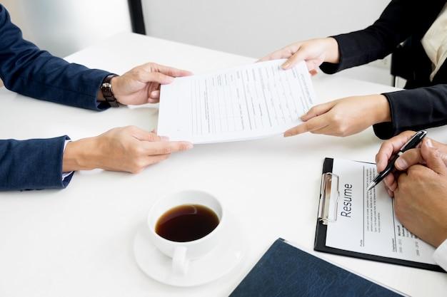 Manos del hombre que da la cartera de la aplicación al hombre de los recursos humanos en oficina para la entrevista.