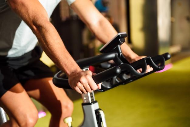 Manos de un hombre que entrena en un gimnasio que hace ciclo interior.