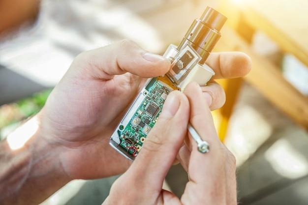 Manos del hombre que fijan el gadget del e-cig del vaporizador moderno para vapear el e-líquido. mantenimiento de equipos electrónicos mech mod vaping device. servicio de reparación de dispositivos vaper.