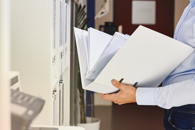 Manos de un hombre que sostiene la carpeta con documentos