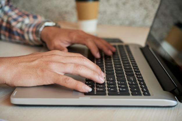 Manos del hombre que trabaja en la computadora portátil