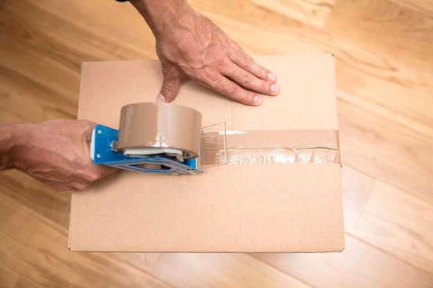 Manos de un hombre que usa un dispensador de cinta para sellar una caja de envío