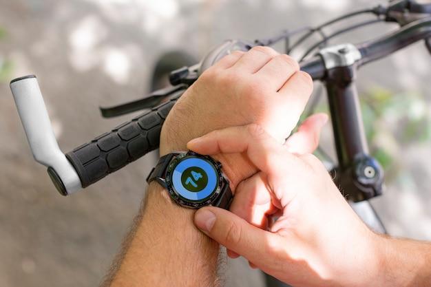 Manos de un hombre con un reloj inteligente en primer plano mientras se monta en bicicleta