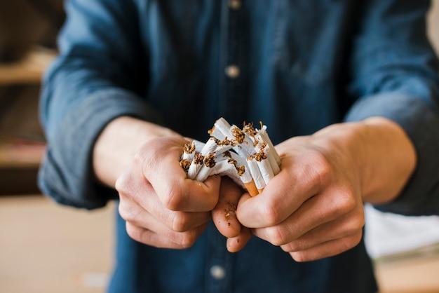 Las manos del hombre rompiendo montón de cigarrillos