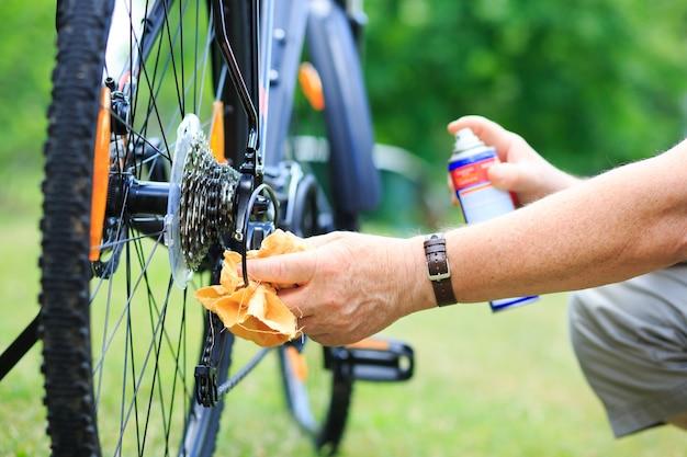 Manos de hombre senior rociar un aceite a la cadena de la rueda de la bicicleta