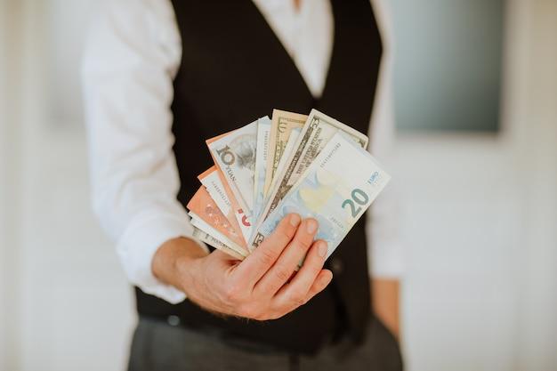 Manos del hombre sosteniendo dinero como euros y dólares sobre fondo blanco.