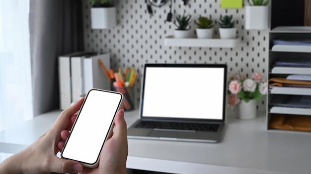 Manos de hombre sosteniendo un teléfono inteligente con pantalla en blanco y sentado en la oficina en casa.