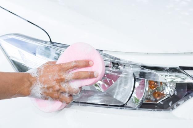 Las manos del hombre sostienen la esponja para lavar el coche blanco