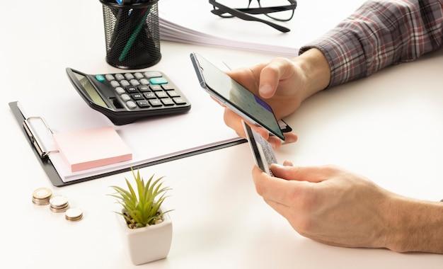 Manos de hombre con teléfono inteligente y computadora portátil para compras en línea en casa, mano que sostiene el teléfono móvil con pantalla de página de detalles de pago y tarjeta de crédito, conceptos de compras en línea
