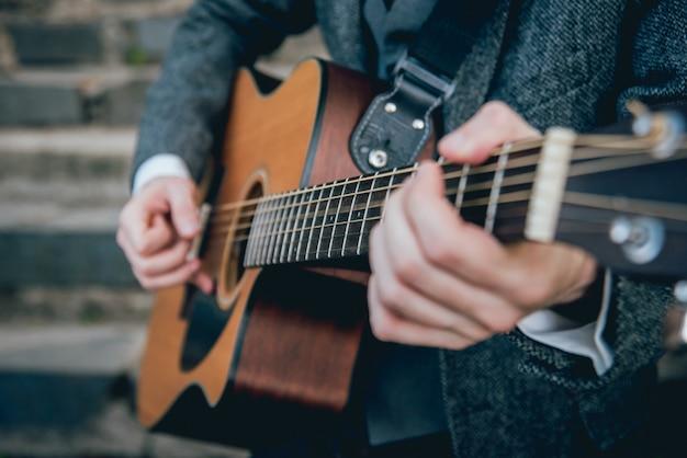 Las manos del hombre tocando la guitarra acústica. auténtico fondo.