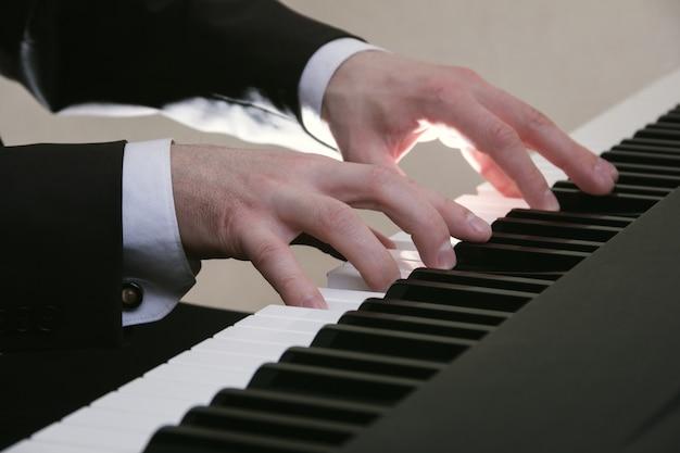 Las manos del hombre tocando el piano en el concierto.