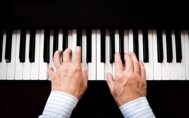 Manos de hombre tocando el piano. música clásica. arte y fondo abstracto.