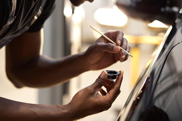 Las manos del hombre usan pincel de detalle para pintar el coche