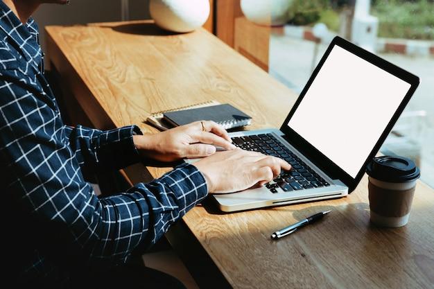 Las manos del hombre usando la computadora portátil con pantalla en blanco en el escritorio en la cafetería.