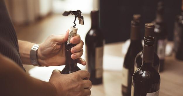 Las manos de los hombres abren una botella de vino con un sacacorchos.