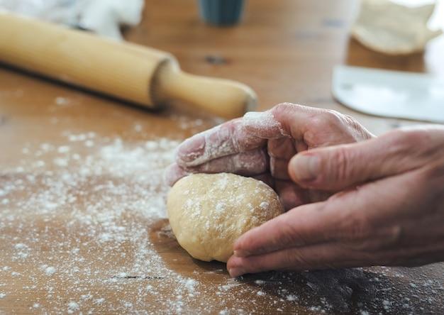 Las manos de los hombres amasan pan en una mesa de madera con harina espolvoreada. concepto de panadería.