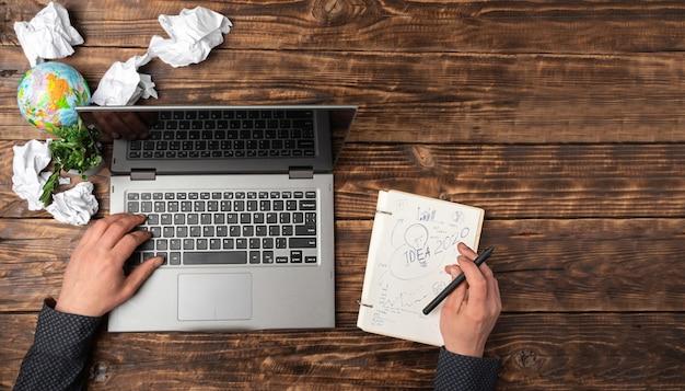 Manos de hombres en una computadora portátil y un cuaderno con ideas en una mesa de madera.