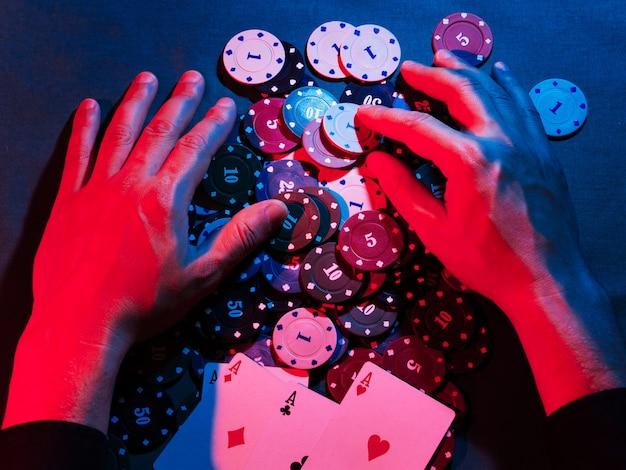 Las manos de los hombres eliminan las fichas de juego colocadas en la apuesta.