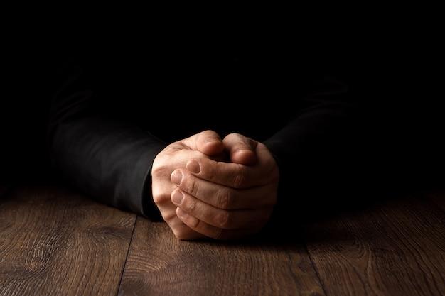 Manos de hombres en oración