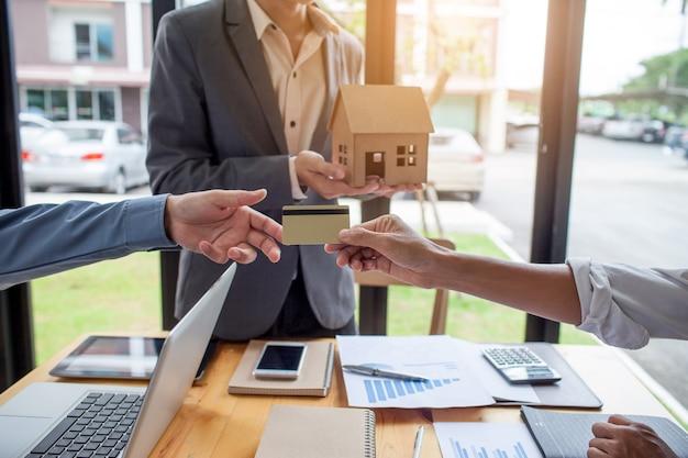 Las manos de los hombres que están entregando tarjetas de crédito a los clientes, el concepto de préstamo hipotecario con c