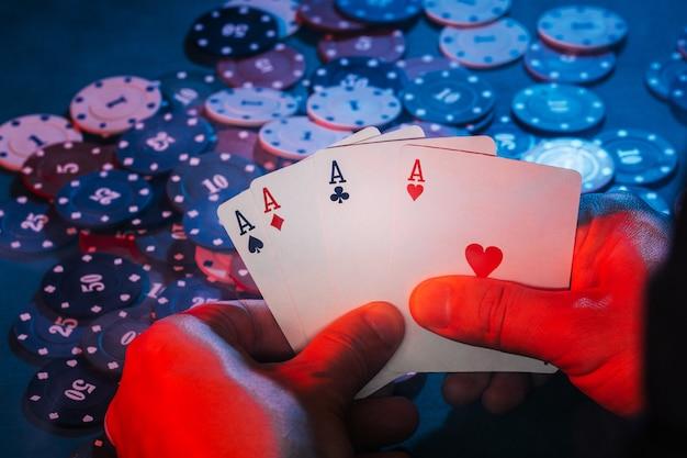 Las manos de los hombres sostienen cartas, un conjunto de ases en el fondo de jugar fichas