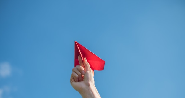 Las manos de los hombres sostienen un cohete de papel rojo con un fondo azul brillante.