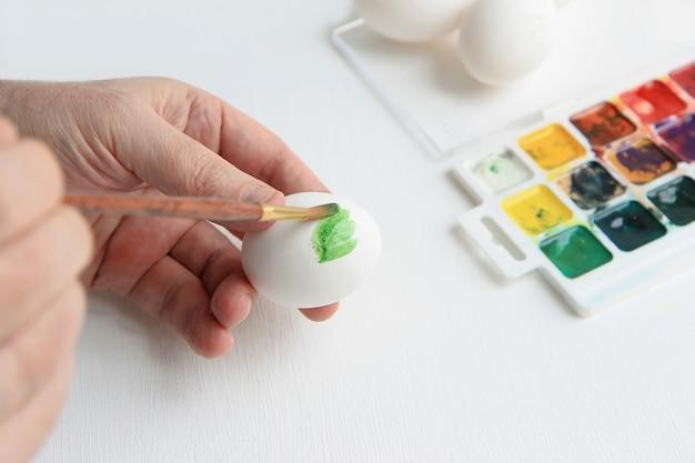 Las manos de los hombres sostienen un pincel y pintan huevos con acuarelas.