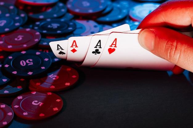 Las manos de los hombres tienen cartas, un conjunto de ases en el juego de fichas