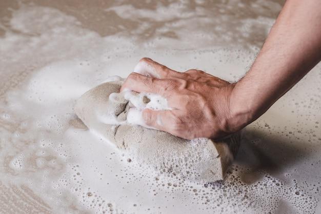 Las manos de los hombres usan una esponja para limpiar el piso de baldosas.