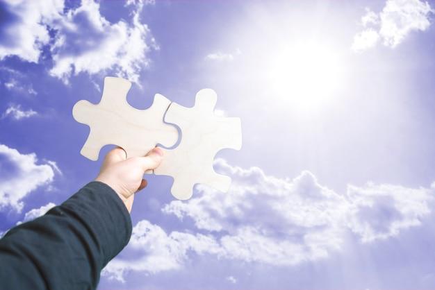 Las manos humanas conectan dos piezas del rompecabezas, toma de decisiones, fondo del cielo
