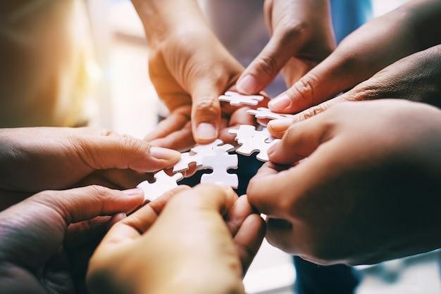 Manos humanas ensamblando un rompecabezas, buscando la pareja adecuada, apoyo en el trabajo en equipo