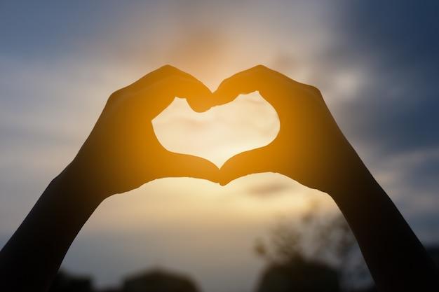 Manos humanas en forma de corazón enmarcado en puesta de sol