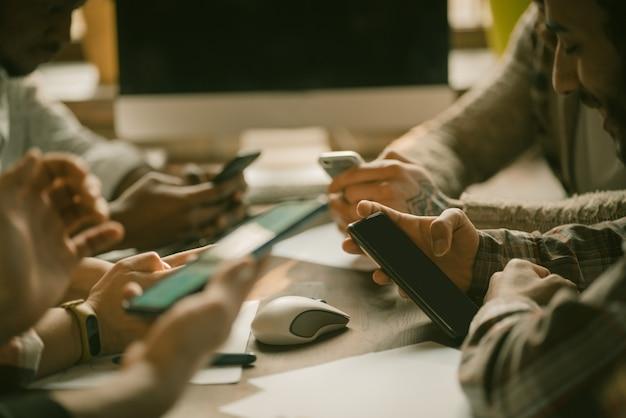 Manos humanas de grupo escribiendo en teléfonos móviles