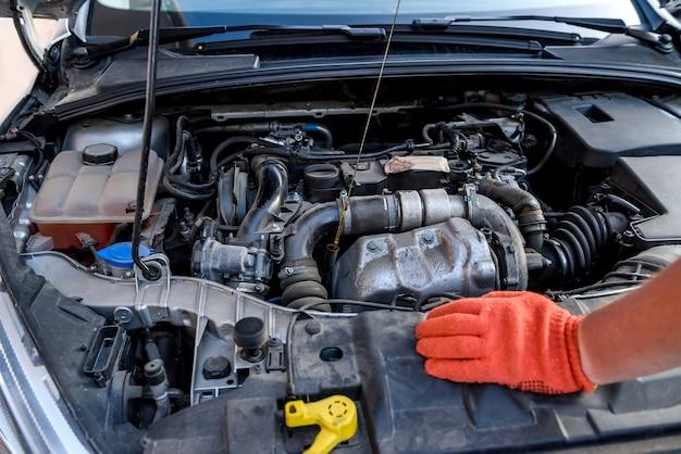 Manos humanas con medidor de nivel de aceite contra el motor del coche