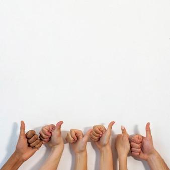 Manos humanas que muestran gesto de pulgar sobre pared con textura blanca