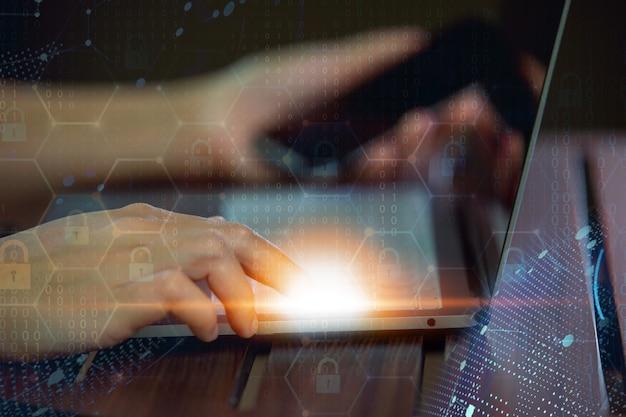 Manos humanas con smartphone trabajando en la computadora portátil en el escritorio de oficina