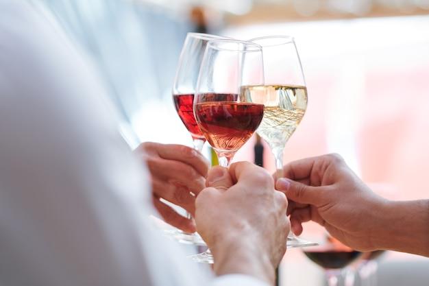 Manos humanas sosteniendo copas de vino con champán, cabernet y brandy mientras tintinean durante el brindis