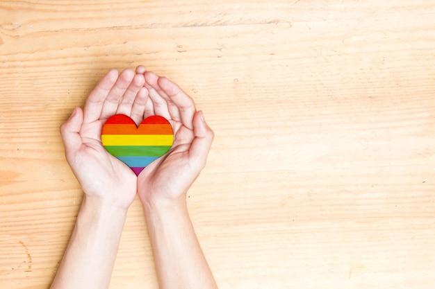 Manos humanas sosteniendo corazón con bandera del arco iris