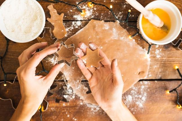 Manos humanas sosteniendo forma para galletas y masa