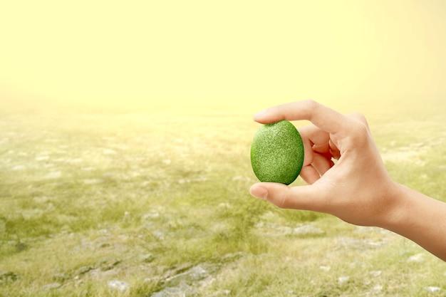 Manos humanas sosteniendo huevos de pascua verdes con campo de pradera. felices pascuas